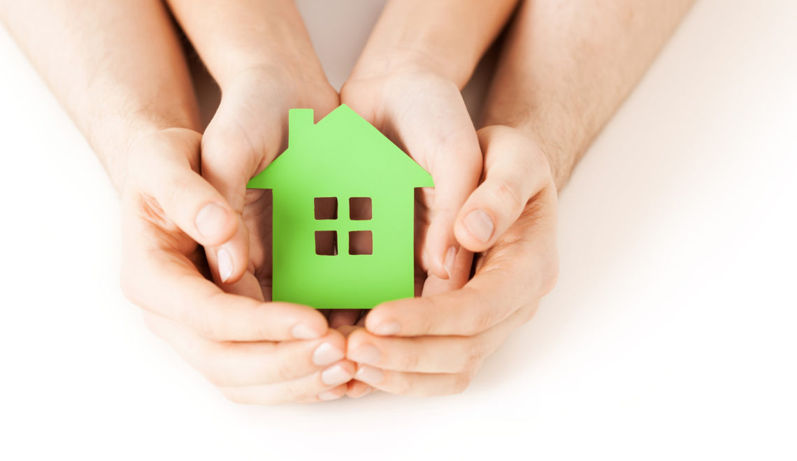 real estate and family home concept - closeup picture of male and female hands holding green blank paper house
